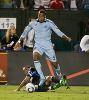 Ramiro Corrales of Earthquakes tries to tackle the ball against Teal Bunbury of Kansas City during the game at Buck Shaw Stadium in Santa Clara. California on October 1st, 2011.  San Jose Earthquakes tied Sporting Kansas City, 1-1.
