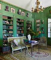 The library features a directoire sofa that retains its original velvet, a 19th century table and chandelier, and an 18th century armchair with its original needlepoint upholstery; the panelling is painted in 'canope' by Zuber