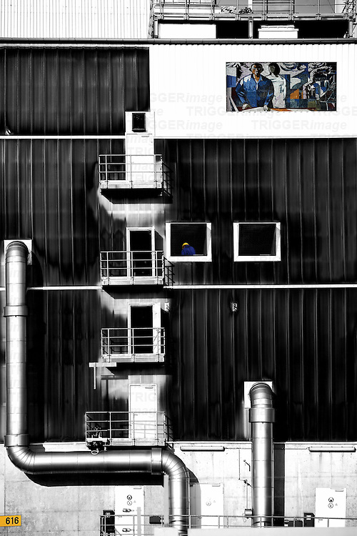 "The collage of an industrial building with workshops and ventilation pipes with the mosaic painting ""Man conquers the cosmos"" of FRITZ EISEL."
