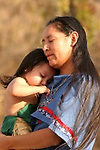 A Native American Indian mom carrying a little toddler who is upset and playing with her turtle beaded necklace