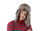 Smiling boy in furry hat on white background