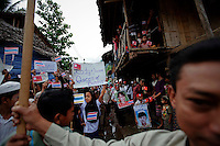 Refugees hold banners and pictures as Nobel Peace Prize winner Aung San Suu Kyi arrives at the Mae La refugee camp where tens of thousands of her compatriots live near Mae Sot at the Thailand-Myanmar border June 2, 2012. Suu Kyi's visit to Thailand, which received widespread media coverage, was her first trip outside Myanmar in 24 years, 15 of which were spent in detention under the junta. REUTERS/Damir Sagolj (THAILAND)