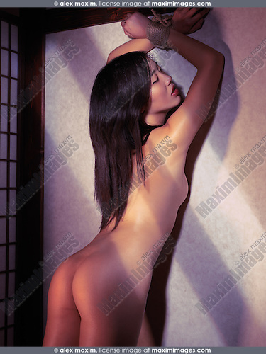 Home Asian Woman Standing Naked At A Wall With Tied Hands
