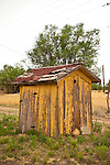 Rustic wooden outhouse behind a house in Encino, New Mex.