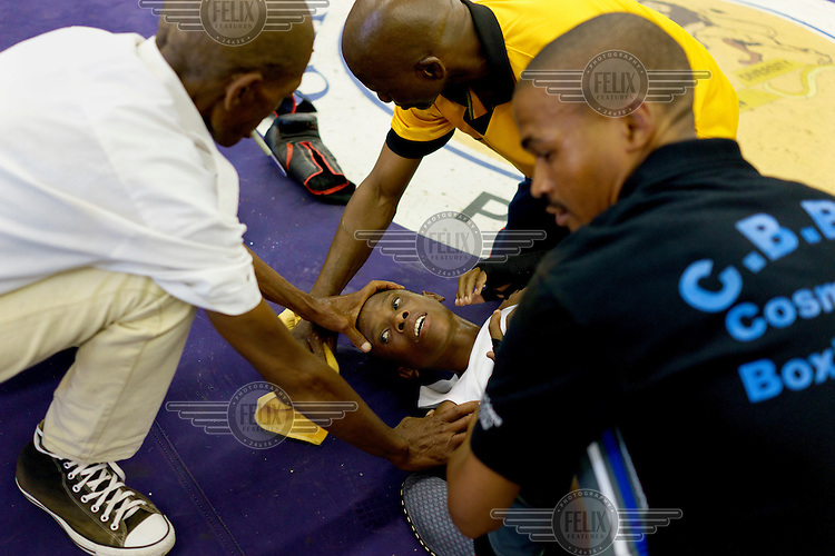 Match officials rush to stabilise a young boxer who has been knocked out during an amateur boxing tournament in Cosmo City, a large low-income housing development 25 kms north of Johannesburg.