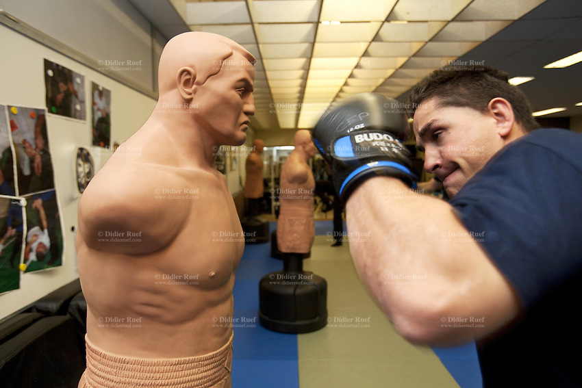 Switzerland. Geneva. A police officer is physically training  at the Police education center (Centre de formation de la Police. CCFP). The policeman is exercising his boxing skills on a dummy with a human appearance. 28.03.12 © 2012 Didier Ruef