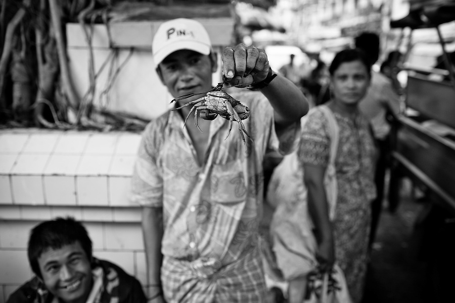 A man shows his crabs for sale in a busy market in downtown Yangon, Myanmar.