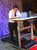 """Change the caption to """"Lee Stranahan of Breitbart.com uploads photos while getting a workout at the Google Hangout journalists' lounge at the Tampa Convention Center. He says that he plans on purchasing a similar desk/ treadmill for home use."""