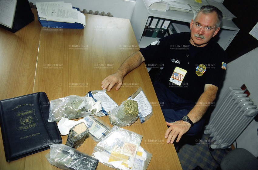 """Yugoslavia. Kosovo. Pristina. Drug addiction. United Nations (UNMIK) Police. Police officer Denis Norton from USA shows illegal drugs seized, heroin and marijuana, but also money seized by police during one month. The establishment of the United Nations Interim Administration Mission in Kosovo (UNMIK) included a large international policing component, named the UNMIK Police. They were given two primary tasks by UN Security Council Resolution 1244: 1) to establish a new police force; 2) in the meantime, to maintain civil law and order. The name for the new police force """"Kosovo Police Service"""", was chosen by the first international police commissioner.© 2001 Didier Ruef"""