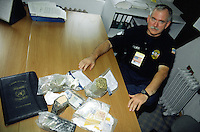 "Yugoslavia. Kosovo. Pristina. Drug addiction. United Nations (UNMIK) Police. Police officer Denis Norton from USA shows illegal drugs seized, heroin and marijuana, but also money seized by police during one month. The establishment of the United Nations Interim Administration Mission in Kosovo (UNMIK) included a large international policing component, named the UNMIK Police. They were given two primary tasks by UN Security Council Resolution 1244: 1) to establish a new police force; 2) in the meantime, to maintain civil law and order. The name for the new police force ""Kosovo Police Service"", was chosen by the first international police commissioner.© 2001 Didier Ruef"