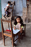 00268_12, Honduras, 2004, HONDURAS-10003. A little girl writes in her work book as her brother plays behind her.