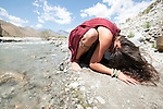 Earth Vibration. Woman in devotional bow to the earth and river.
