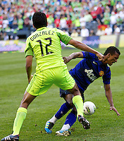 Manchester United midfielder Nani slides into Seattle Sounders FC defender Leonardo Gonzalez during play at CenturyLink Field in Seattle Wednesday July 20, 2011. Manchester United won the match 7-0.