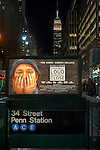 "Manhattan, NY, USA - January 9, 2012: Movie poster ""Extremely Loud & Incredibly Close"" hangs illuminated at night over Penn Station subway entrance with Empire State Building in background. At stairwell entrance to the MTA (Metropolitan Transit Authority) 34 Street Penn Station subway station. [Fictional movie is set at time of 9/11 terrorist attacks on Twin Towers in NYC.]"