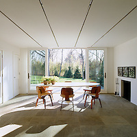 A wall of glass allows sunlight to pour in to the dining room furnished with a Saarinen table and Eames chairs.