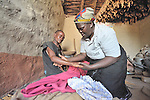 Home-based care worker Olipa Mkandawire (right), cares for a man living with AIDS in Matuli, Malawi. She represents the Livingstonia Synod AIDS Program of the Church of Central Africa Presbyterian.