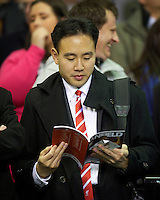 LIVERPOOL, ENGLAND - Thursday, October 4, 2012: Liverpool Director of Communications Jen Chang reads the match-day programme as the Reds take on Udinese Calcio during the UEFA Europa League Group A match at Anfield. (Pic by David Rawcliffe/Propaganda)