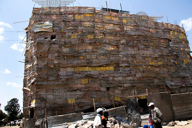 A building under construction, covered with cement bags.