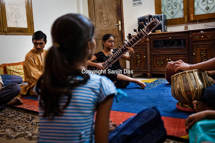 12 year old Aayushi Dwedi plays sitar in a class while other students look on in a music class at the Academy of Indian Classical Music in Varanasi in Uttar Pradesh, India. Photograph: Sanjit Das/Panos
