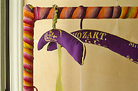A pair of hangers covered in a purple fabric with a Mozart script on a clothes rail wrapped in coloured ribbon