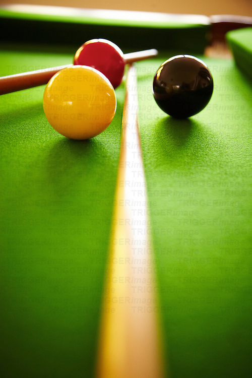 red white and black billiard balls on green baize