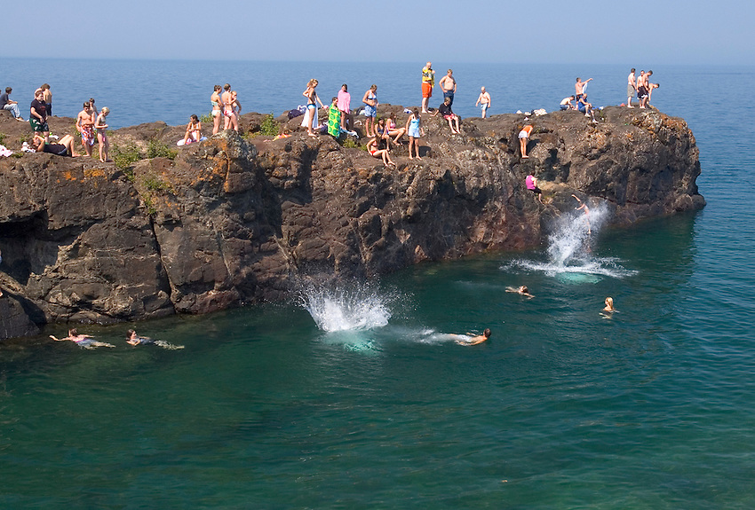 People sun bathe and dive into Lake Superior at the Black Rocks area of Presque Isle Park in Marquette, Mich. on a hot summer day.