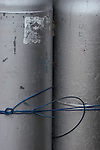 Two propane cyllinders tied together by blue colored copper wire