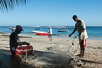 Fisherman Herve Mariane (seated) repairs his nets. Morning. Tamarin.