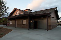 A 3/4 view of the front of the restroom and storage building building at Stanton Central Park at sunset.  Two tile photographs illustrate the front wall and the roof has some neat details.  A cloudy sky makes up the top.
