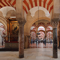 The hypostyle prayer hall, area built in the 10th century under Al-Hakam II, 961-976, with a cathedral altar and behind, the area built under Al-Mansur, 987-988, in the Cathedral-Great Mosque of Cordoba, in Cordoba, Andalusia, Southern Spain. The hall is filled with rows of columns topped with double arches of a horseshoe arch topped by a Roman arch, in stripes of red brick and white stone. The first church built here by the Visigoths in the 7th century was split in half by the Moors, becoming half church, half mosque. In 784, the Great Mosque of Cordoba was begun in its place and developed over 200 years, but in 1236 it was converted into a catholic church, with a Renaissance cathedral nave built in the 16th century. The historic centre of Cordoba is listed as a UNESCO World Heritage Site. Picture by Manuel Cohen