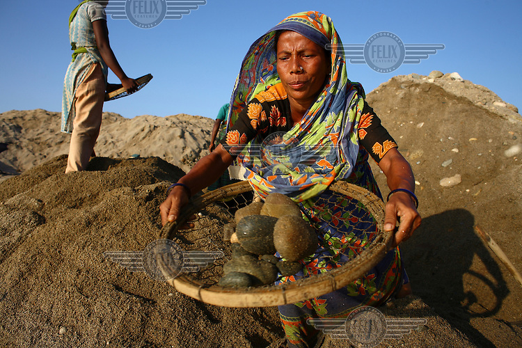 A woman works at Bhollar Ghat. At least 10,000 people, including 2,500 women and over 1,000 children, are engaged in stone and sand collection from the Bhollar Ghat on the banks of the Piyain river. Building materials such as stone and sand, and the cement which is made from it, are in short supply in Bangladesh, and commands a high price from building contractors. The average income is around 150 taka (less than 2 USD) a day.