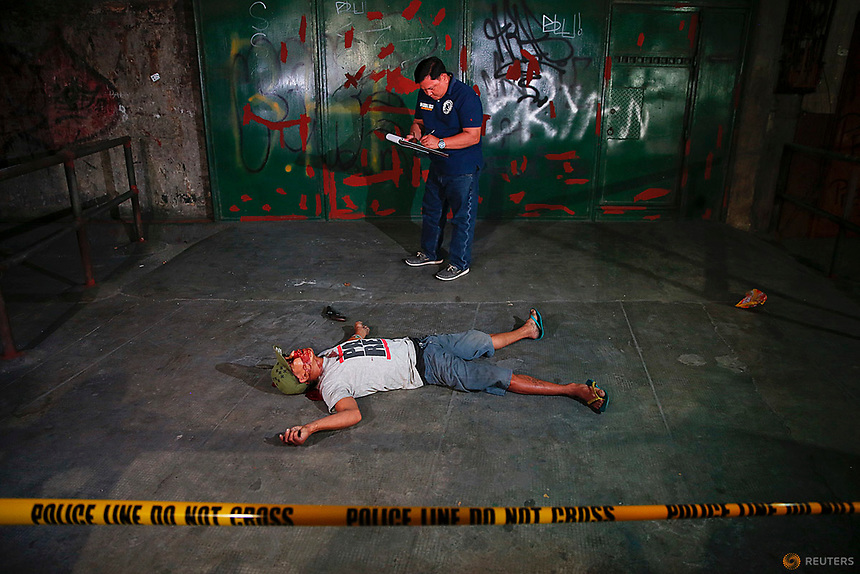 An investigator takes notes next to the body of a man killed in a shootout with police in Manila, Philippines early October 21, 2016. According to the police, sachets containing substance believed to be drug shabu (Metamphetamine Hydrochloride) were found in killed man's pockets. REUTERS/Damir Sagolj
