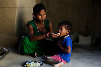 Pramila Tharu, 15, feeds lentils and rice to her 2 year old toddler Prapti, in Bhaishahi village, Bardia, Western Nepal, on 29th June 2012. Pramila eloped and married at 12 and gave birth to Prapti at age 13. She delivered prematurely on the way to the hospital in an ox cart and her baby weighed only 1.5kg at birth. In Bardia, StC works with the district health office to build the capacity of female community health workers who are on the frontline of health service provision like ante-natal and post-natal care, especially in rural areas. Photo by Suzanne Lee for Save The Children UK