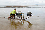 The Last Mudhorse Fishermen. UK 2008. The Sellick family, Stolford, Bridgewater Bay, Somerset. Adrian pushing the Mudhorse out to the fishing netts at low tide.