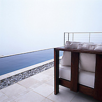 Infinity pool along the edge of Table Mountain with a misty sea view beyond.