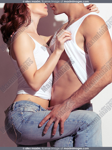 Sexy couple portrait of a young woman pulling man's tank top up, revealing his muscular body