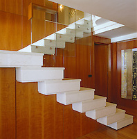 The white marble staircase has walls clad in cherrywood and a balustrade made of glass panelling