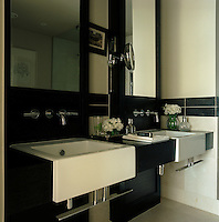 The contemporary bathroom has matching white enamel wash basins set within a black wooden surround