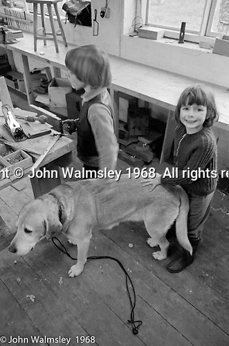 Stroking Neill's dog in the carpentry room, Summerhill school, Leiston, Suffolk, UK. 1968.