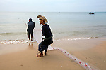 Two fishermen pull in a net on the beach in Mui Ne, Vietnam. Nov. 20, 2011.