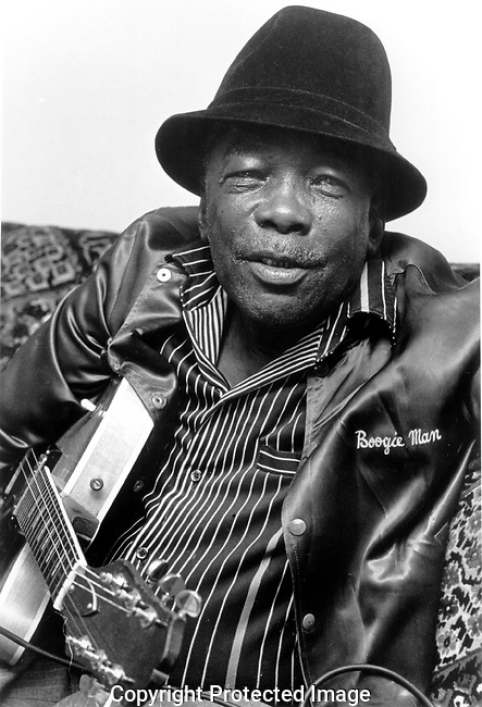 John Lee Hooker, 6/20/84. American blues singer-songwriter and guitarist, born near Clarksdale, Mississippi, who rose to prominence performing his own unique style of what was originally closest to Delta blues. Though similar to the early Delta blues, his music was metrically free. John Lee Hooker could be said to embody his own unique genre of the blues, often incorporating the boogie-woogie piano style and a driving rhythm into his masterful and idiosyncratic blues guitar and singing.