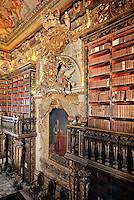 Black Room of the Joanina Library, or Biblioteca Joanina, a Baroque library built 1717-28 by Gaspar Ferreira, part of the University of Coimbra General Library, in Coimbra, Portugal. The bookshelves were made, gilded and lacquered by Manuel da Silva and the portrait is of King John V or Joao V, 1689-1750, by Domenico Dupra, 1725, topped by a gilded sculptural crown and angels, exalting the King and Portugal. The Casa da Livraria was built during the reign of King John V or Joao V, and consists of the Green Room, Red Room and Black Room, with 250,000 books dating from the 16th - 18th centuries. The library is part of the Faculty of Law and the University is housed in the buildings of the Royal Palace of Coimbra. The building is classified as a national monument and UNESCO World Heritage Site. Picture by Manuel Cohen
