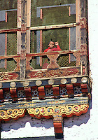 Child watching from carved decorative window, Thimpu, Bhutan