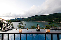A hotel attendant prepares to light the lanterns that surround this infinity pool