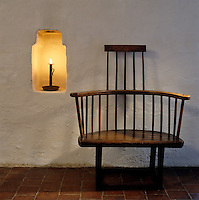 A candle stands in a niche next to a rustic wooden armchair