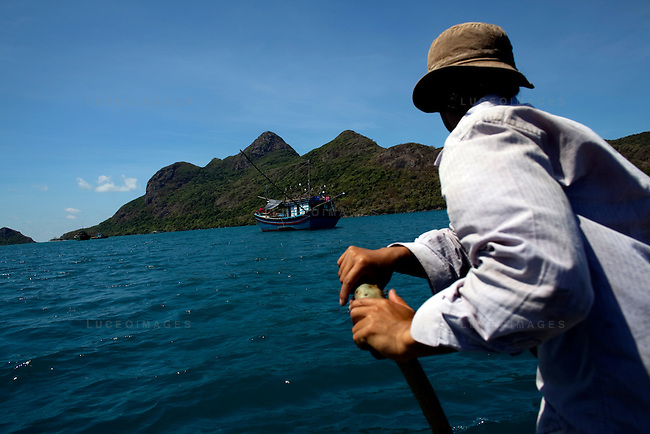 Luong, 27, a fisherman, rows his small circular boat back to the main island in front of Tre Lon Island, part of the Con Dao Islands in Vietnam. The 16 mountainous islands and islets are situated about 143 miles southeast of Ho Chi Minh City in Vietnam, in the South China Sea. Photo taken Thursday, May 5, 2010...Kevin German / LUCEO For the New York Times