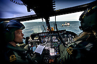 Pilots in a Lynx helicopter monitor the progress of the Fade I cargo ship, a WFP (World Food Programme) ship delivering 5,000 tonnes of food aid to Somalia. Many aid ships have been hijacked by pirates in these waters, and the Dutch Navy monitor the vessels to try and prevent further attacks.