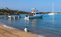 A boy sitting in gentle surf watches tour boats load up at 'Anaeho'omalu Bay, Big Island.