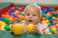 One Year Old Caucasian Baby Girl in Playground with Toy Balls