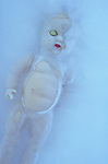 Traditional baby doll with eyes closed lying as if dead or asleep in sheet of ice